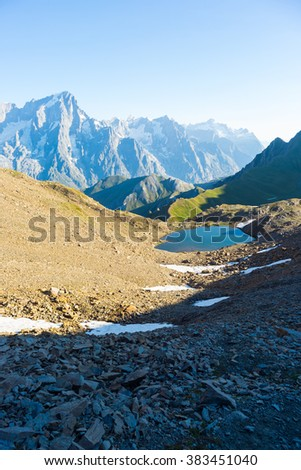 High mountain trail with great panoramic view over the Mont Blanc massif and blue lake. Backpacker's summer adventures and wanderlust in Valle d'Aosta, Italian French Alps. - stock photo