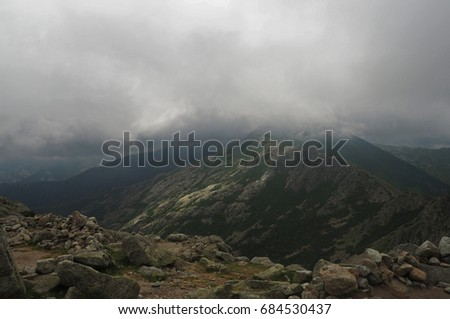 high mountain view scenery with the storm clouds and fog and granite rock