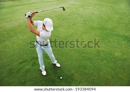 High overhead angle view of golfer hitting golf ball on fairway green grass - stock photo