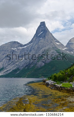 High peak (Stetind) rises from fjord in northern Norway - stock photo
