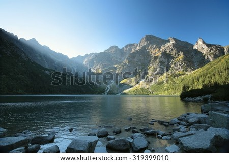 High peaks of the Tatra mountains on the edge of the lake. - stock photo