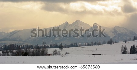 High polish Tatra Mountains with clouds and sun coming through in winter. Trees covered with hoarfrost. Panorama view - stock photo