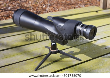 High powered spotting scope set up on a bench - stock photo