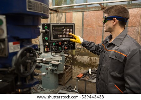 High precision equipment. Male operator pushing buttons turning on the CNC high precision milling machine modern metalworking processing technologies concept