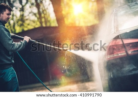 High Pressured Water Car Cleaning and Washing. Springtime Backyard Car Washing. - stock photo
