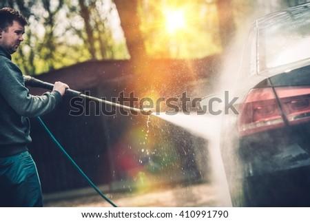High Pressured Water Car Cleaning and Washing. Springtime Backyard Car Washing. - stock photo