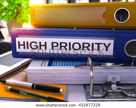 High Priority - Blue Office Folder on Background of Working Table with Stationery and Laptop. High Priority Business Concept on Blurred Background. High Priority Toned Image. 3D. - stock photo