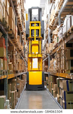 High rack stacker forklift truck in warehouse row - stock photo