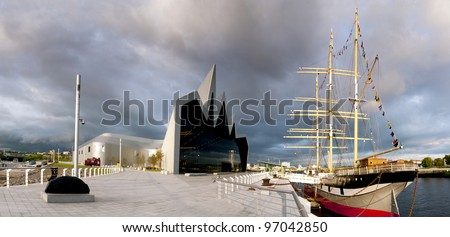 High resolution panorama of the River Clyde in Glasgow featuring the Riverside Museum and Tall Ship. The sun is setting as storm clouds gather.