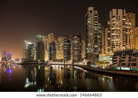 High rise apartments against the dark night. Calm water of the artificial canal reflects skyline