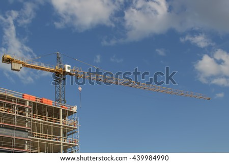 High rise building construction site with cranes against blue sky. Place for text. - stock photo