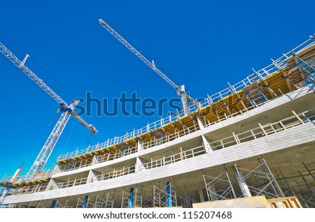 High-rise building under construction. The site with cranes against blue sky. Vancouver, Canada. - stock photo