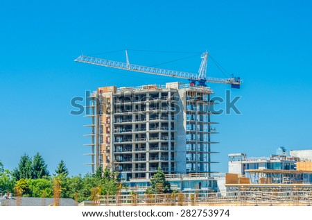 High rise building under construction. The site with cranes against blue sky. Vancouver, Canada. - stock photo