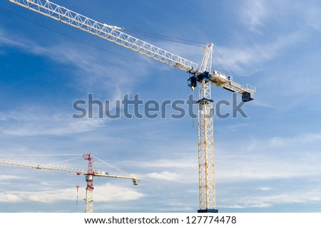 High-rise building under construction. The site with cranes against blue sky with white clouds - stock photo