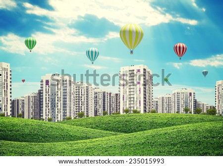 high-rise buildings over green hills, a few air balloons above