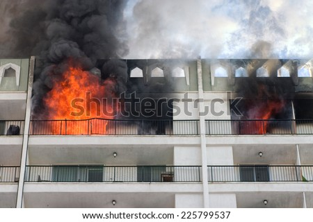 High rise condominium or apartment fire with flames coming out the windows.