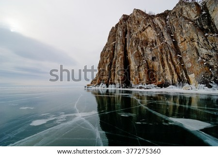 High rocky cliff and clear black ice on the Baikal Lake in winter, Siberia, Russia - stock photo