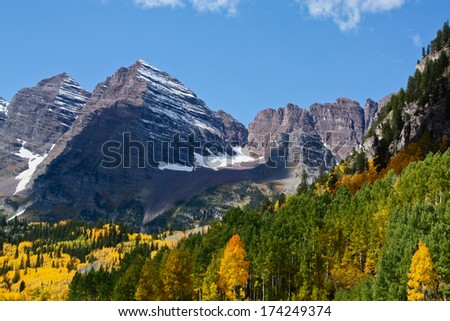 High Rocky Mountain Maroon Peak With Golden and Green Aspen Trees in Autumn - stock photo