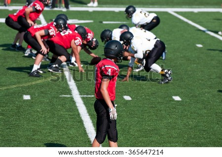 High School American football receiver waiting for play to start during the game. - stock photo