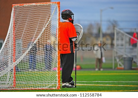 High School boys Varsity lacrosse goalie stands at the ready to protect his gate from the opponents. - stock photo