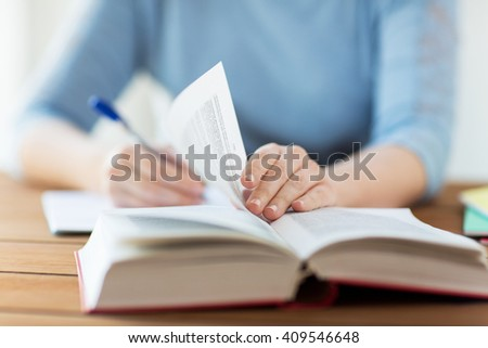 high school, education, people and learning concept - close up of young student or woman with book writing to notebook at home - stock photo