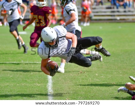 High School Football Player diving forward for a first down