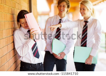 high school girl being bullied by classmates - stock photo