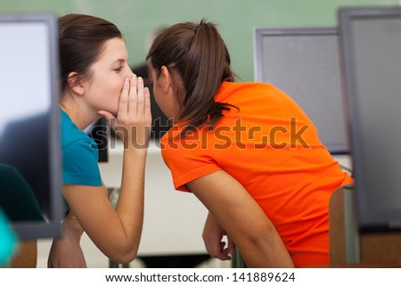 high school girls gossiping in class during a lesson - stock photo