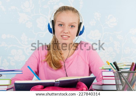 High school student making homework at desk with music on headphones - stock photo