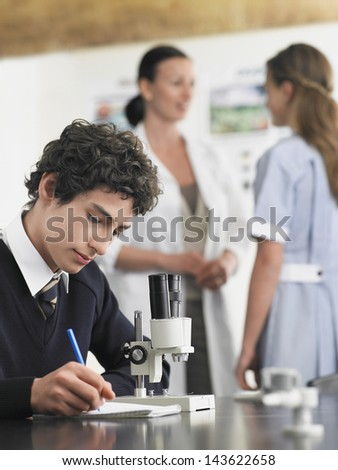 High school student using microscope and taking notes in laboratory - stock photo