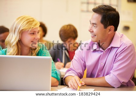 High School Student With Teacher In Class Using Laptop