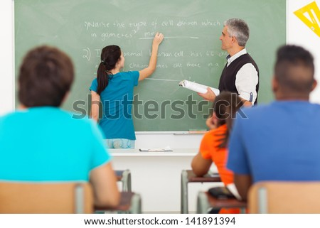 high school student writing an answer on the chalkboard during biology lesson - stock photo