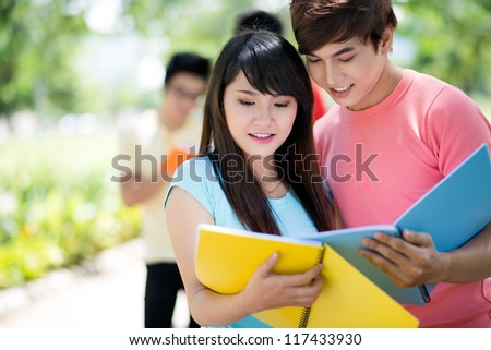 High-school students comparing homework before the lesson - stock photo