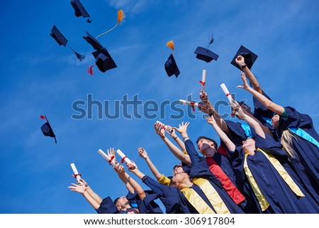 high school students graduates tossing up hats over blue sky.
