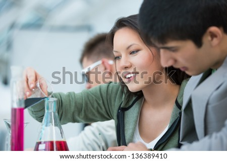 High School students. Group of students working at chemistry class: mixing reagent liquids and using glassware - stock photo