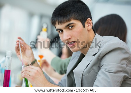 High School students. Handsome mixed race guy working at laboratory class