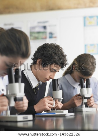 High school students using microscopes in laboratory