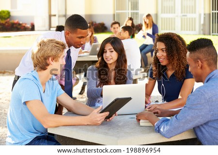 High School Students Working On Campus With Teacher - stock photo