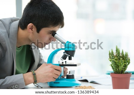 High School students. Young handsome male student looking through microscope biological sample in science classroom - stock photo