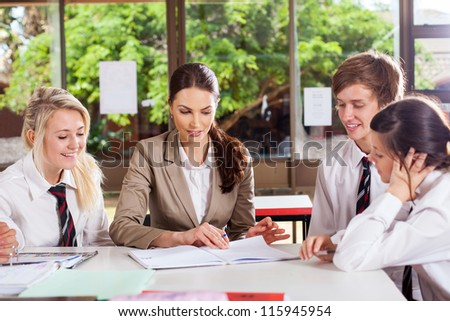 high school teacher helping students in classroom - stock photo