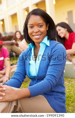 High School Teacher Sitting Outdoors With Students On Campus - stock photo