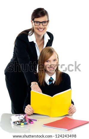 High school teacher standing behind cheerful student. Both looking at the camera. - stock photo