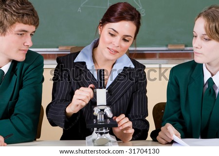 high school teacher teaching microscope to her students - stock photo