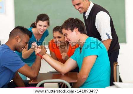 high school teenage boys arm wrestling in classroom