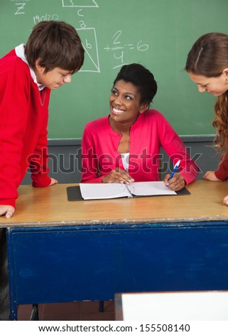 High school teenage students with young teacher at desk in classroom - stock photo