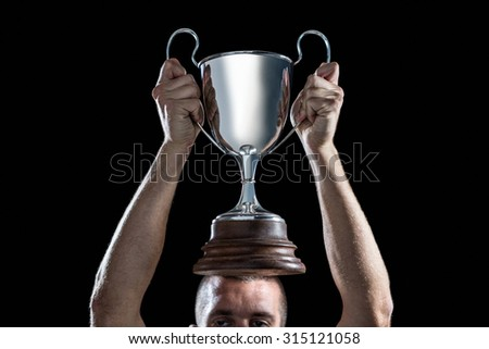 High section of successful rugby player holding trophy against black background - stock photo