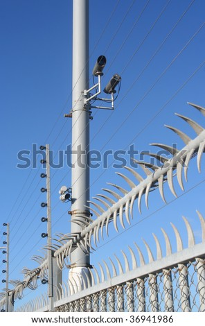 high security fence with video cameras and electric wire
