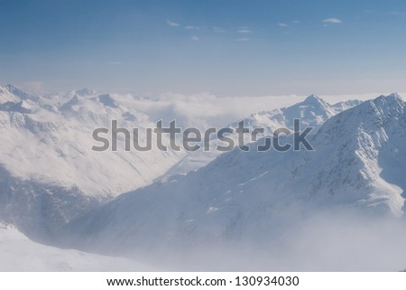 High snow covered peaks of the Austrian Alps, with white clouds below and blue sky above.