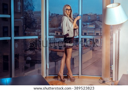 High society blonde woman in glasses with cup of tea by the large window with city views . Business woman drinks tea. City views behind the window in the office. Business concept.