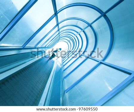 high-speed moving escalator in tube to underpass - stock photo